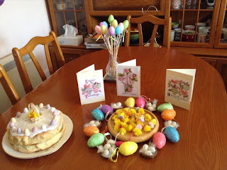 an old photo of a table layout at easter with an easter cake and egg decorations