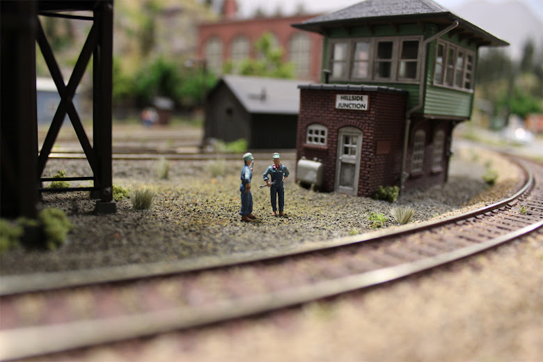 Two train mechanics from a Woodland Scenic Accents kit chat alongside railroad track and a signal tower