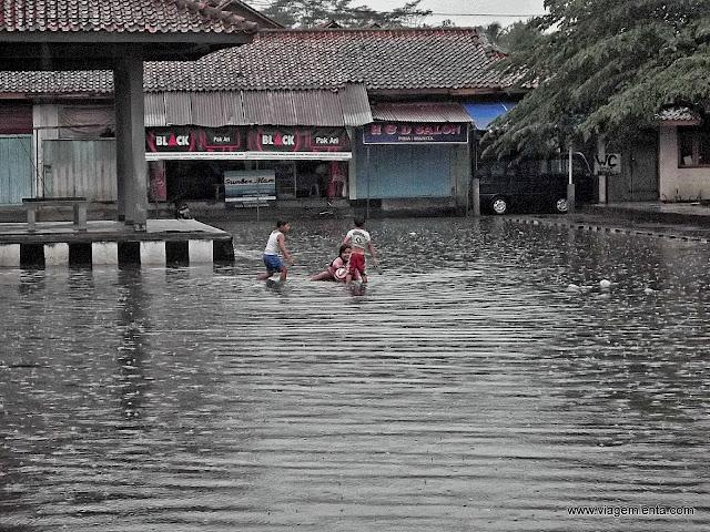 Crianças brincam na cidade inundada após a chuva