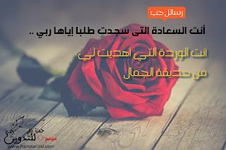 رسالة شوق قضيرة مكتوبة بشكل جميل ورمانسي على صورة وردة حمراء كالورود التي يقدمها العشاق لحبيباتهم