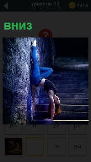 Девушка стоит около стенки головой вниз в стойке на руках в джинсах и топике на ступеньках