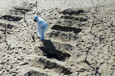Volunteers dug 100 shallow graves symbolizing the COVID-19 deaths in the country.