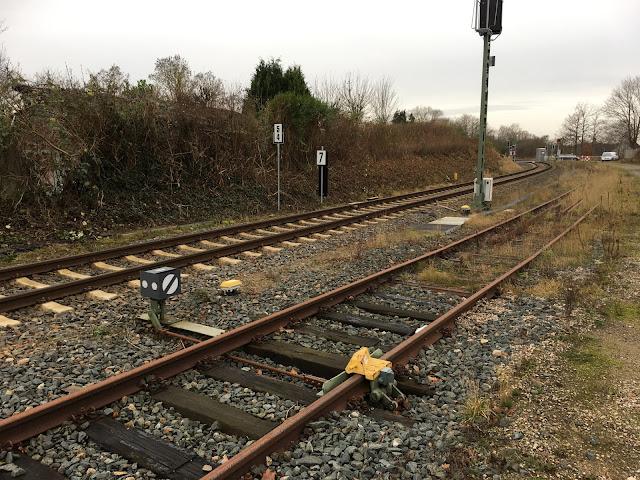 Die beiden Schienstränge parallel nach hinten aus dem Bild laufend. Vorn sind für das Abstellgleis ein Signal für die Weiche und vermutlich eine Gleissperre in orange. Das Abstellgleis ist zugewuchtert. Ein hoher Signalmast ragt zwischen den Gleisen auf. Links stehen am kleinen Hang zwei Zahlen-Tafeln mit 5 und 4 untereinander und einer 7. Im Hintergrund ist der Bahnübergang und das kleine graue Häuschen zu sehen.