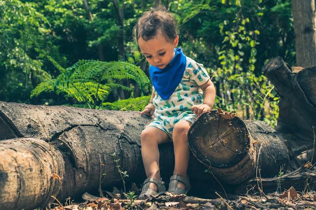 Criança usando macaquinho geométrico em meio a natureza
