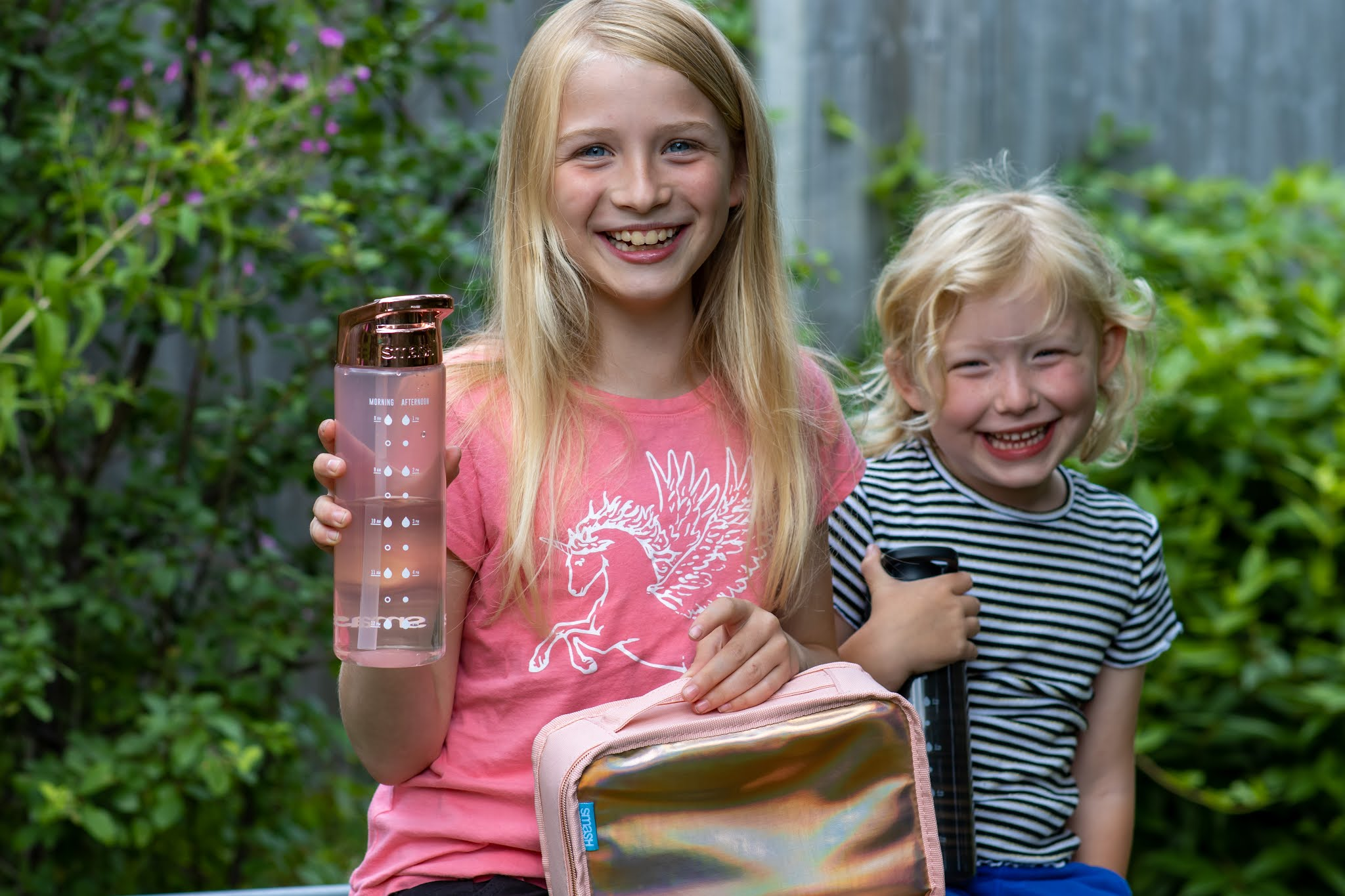 Two girls in a garden one with a SMASH rose gold water bottle and rose gold iridescent lunch bag, the other with a black water bottle