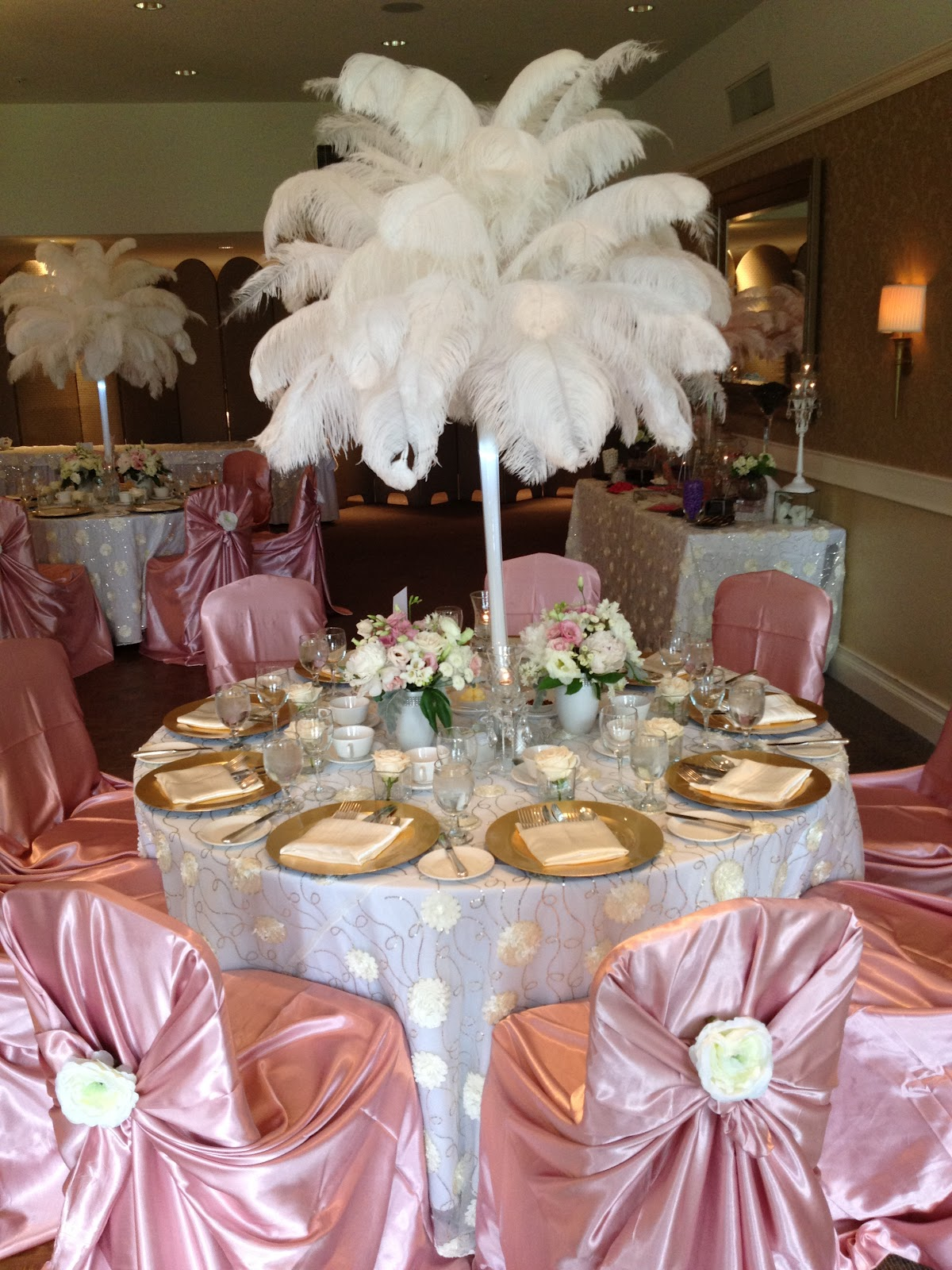 The Flowers Were Placed Underneath Large White Ostrich Centerpieces And On Chair Covers Pulled Look Together