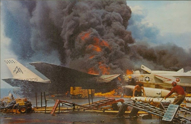 Image Attribute: Photo of the fire aboard the U.S. Navy aircraft carrier USS Forrestal (CVA-59) on July 29, 1967, off Vietnam. Two North American RA-5C Vigilante aircraft of heavy reconnaissance squadron RVAH-11 Checkertails are burning on the starboard side aft of the island, while crewmen remove AGM-45 Shrike missiles in the foreground. / Source: US Navy