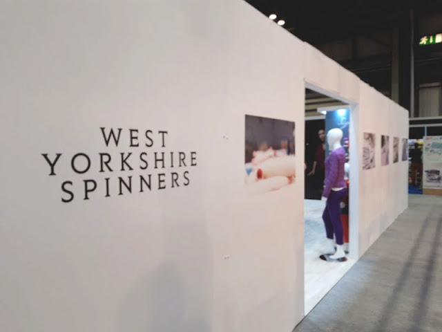 Image shows a white wall leading to an entrance where you can see a mannequin wearing a purple jumper.  The words West Yorkshire Spinners are written on the wall in black print
