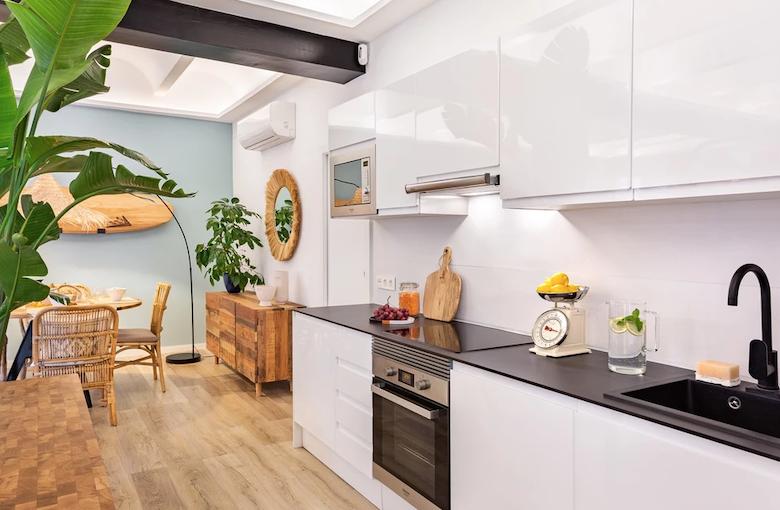 Cocina abierta al salón con decoración de inspiración tropical.