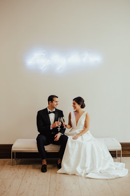 bride and groom with neon sign