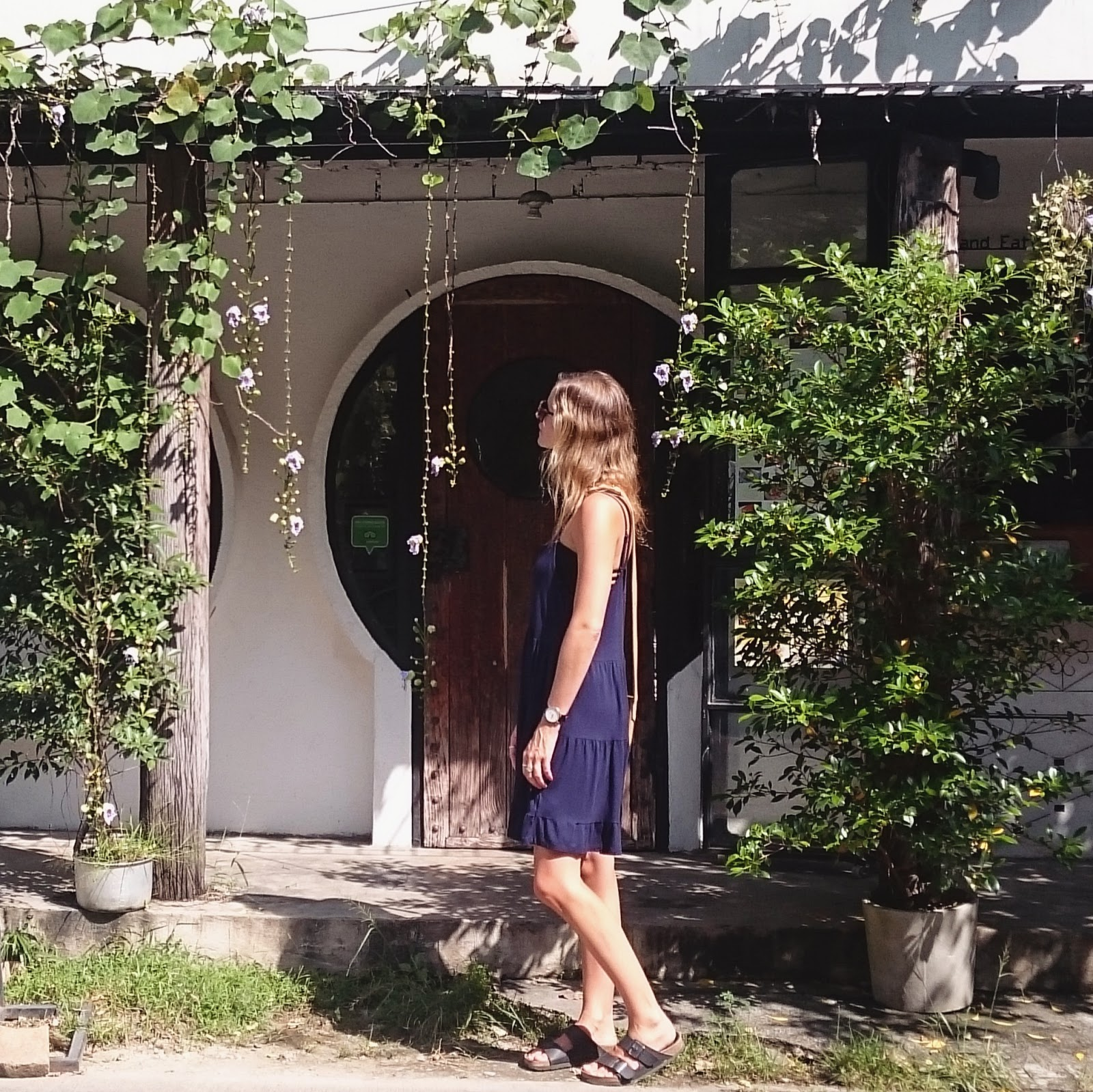 Travel blogger and digital nomad, Alison Hutchinson, is standing in front of a picturesque restaurant in Chiang Mai, Thailand