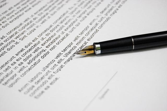 Foto imagem de um documento sendo assinado.