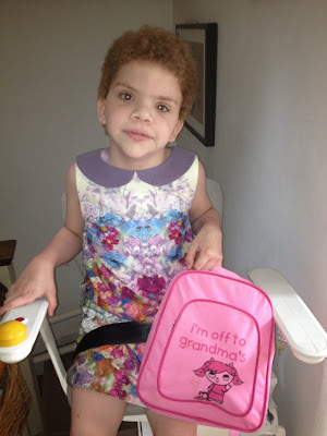 Daisy sitting on a stairlift in a pretty dress holding a pink rucksack