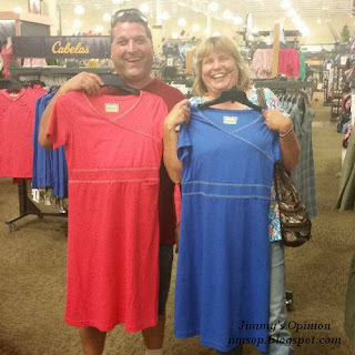 Robbie and Cindy holding dresses in front of themselves while shopping