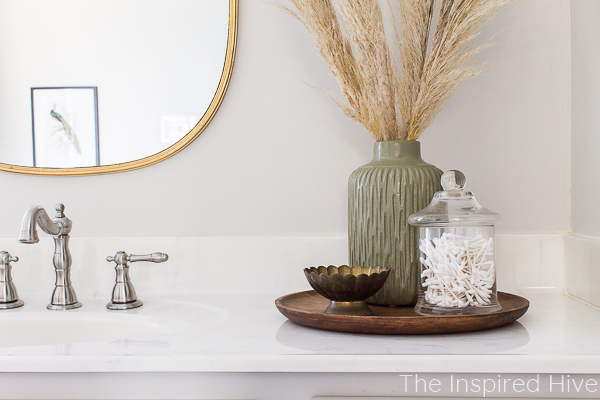 Master bathroom vanity with gold mirror and nickel faucet