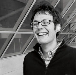 Ilya Kaminsky stands in an alcove with large windows. He is laughing and his eyes have closed. He has short, medium dark hair and wears glasses. He is wearing a striped button-down shirt and a dark pullover with a zipper.