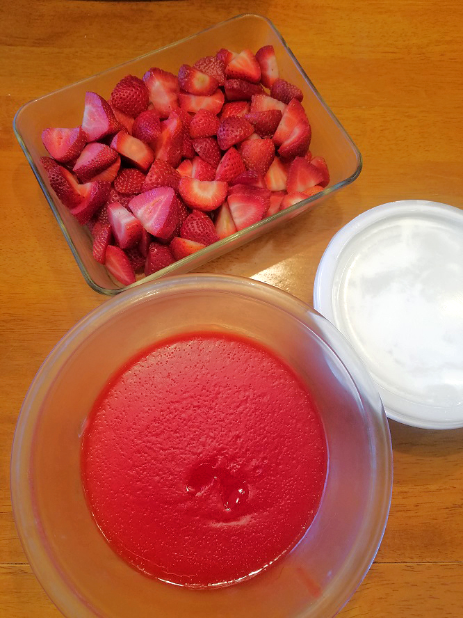 this is a bowl of jello and pudding and a dish of freshly cut strawberries. A bowl of cool whip in a plastic container is on the side