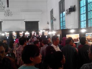 Pengunjung pameran asyik mengamati berbagai foto yang dipajang