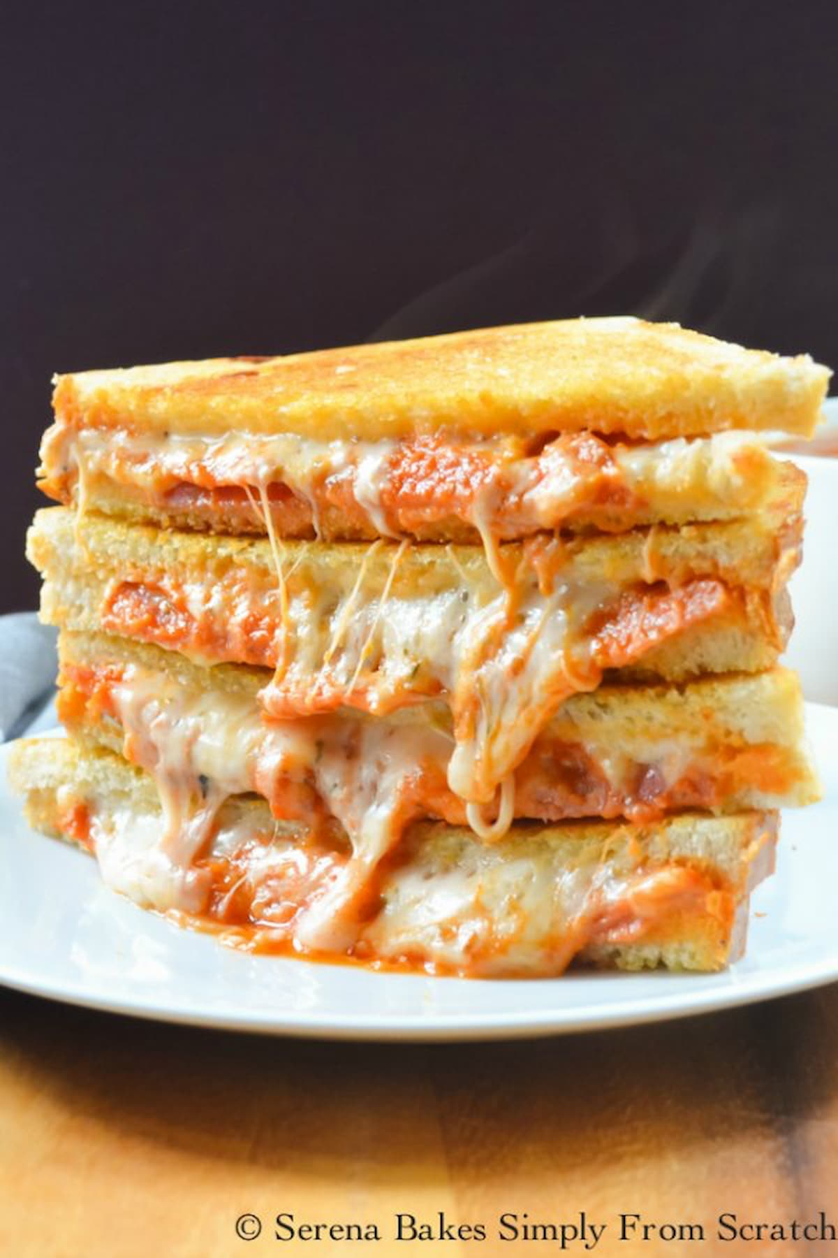 Pepperoni Pizza Grilled Cheese Sandwich stacked on a plate with Cheese pulling out of the sandwiches .