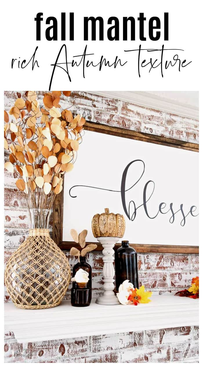 fall mantel with blessed sign, wicker wrapped bottle, fall leaves and amber glass jars