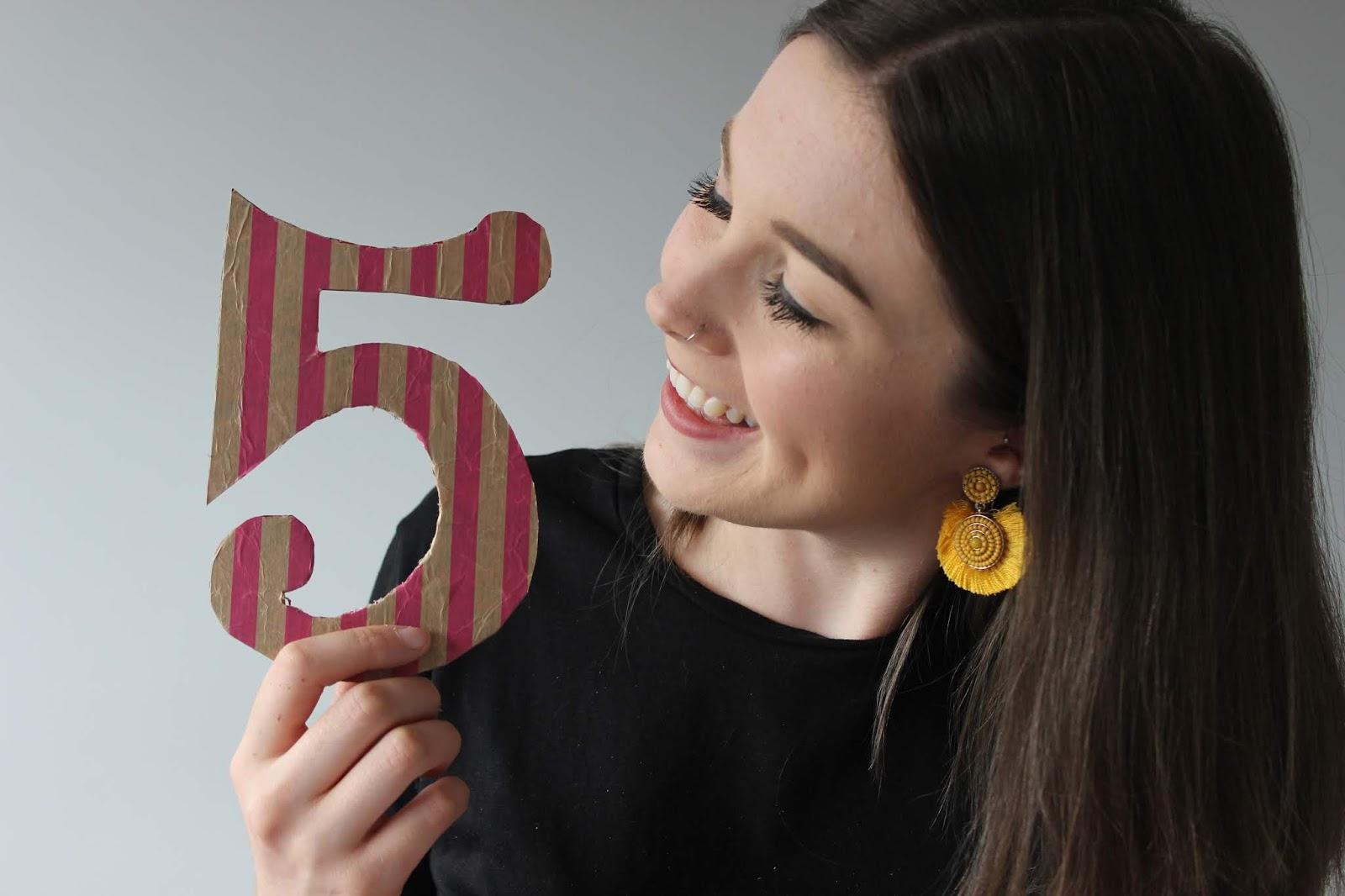 Chloe Elizabeth holding a number five banner
