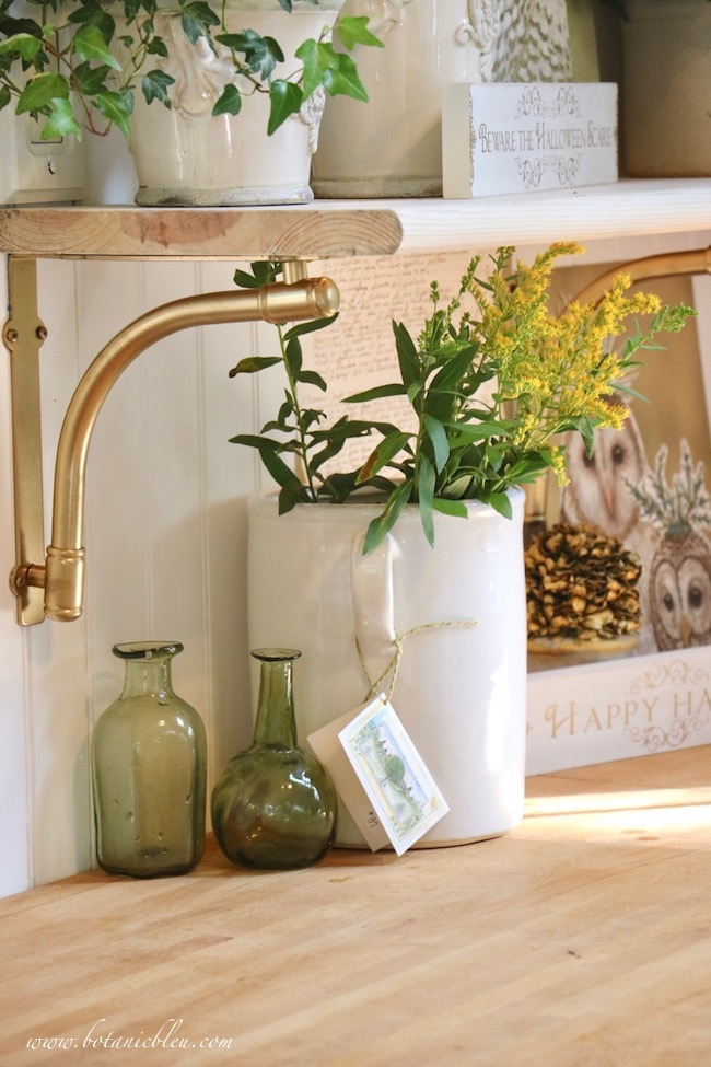 Gold spray paint transforms metal shelf brackets into elegant supports for French Country open shelves