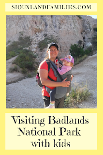 """a mom in a pink shirt and black baseball cap holds a toddler in a purple and white hat in a slate blue carrier while the pair stands in front of a rock formation at Badlands National Park. below the image, the words """"visiting Badlands National Park with kids"""" and above the picture, """" SiouxlandFamilies.com"""""""