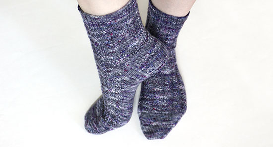 Casually posed feet wearing hand knit wool socks in shades of gray with spots of purple against a white background.