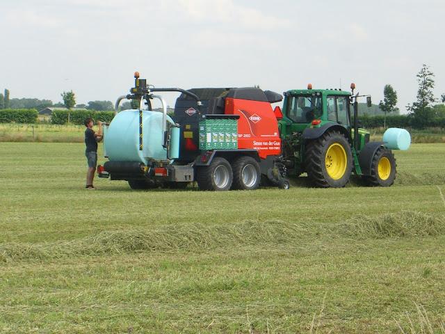 Landbouwwerktuig dat balen maakt van gedroogd gras met zo'n groen plasticje.