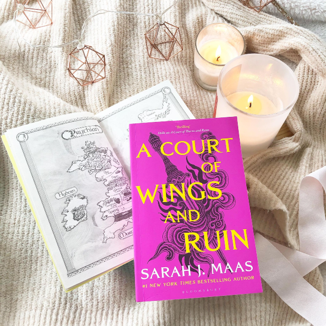 Bright pink cover of 'A Court of Wings and Ruin' by Sarah J Maas on a beige jumper next to a candle