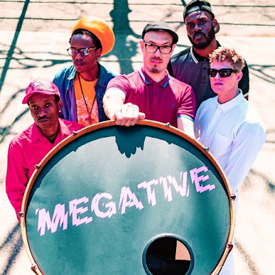 The band poses in back of a drum head with Megative printed on it.