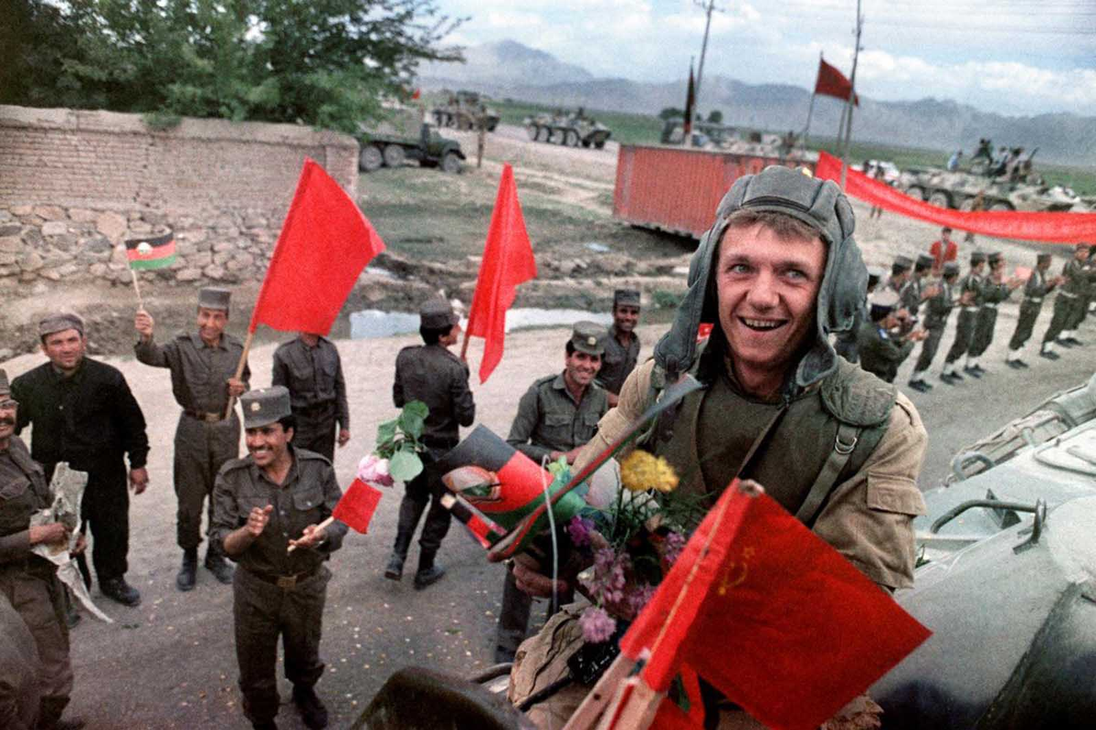 A Red Army soldier atop of his armored personal vehicle smiles as Soviet Army troops stop in Kabul prior to their withdrawal from Afghanistan, on May 16, 1988.