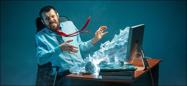 شاب مرهق رجل أعمال وسيم يعمل على مكتب في مكتب حديث يصرخ على شاشة الكمبيوتر المحمول ويغضب من البريد الإلكتروني العشوائي.  ملصقة بجبل من الورق المجعد.