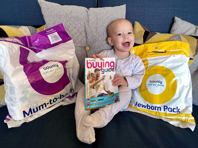 A baby sitting on a sofa holding a Bounty Buying Guide and sitting between a Bounty Mum-To-Be pack and Newborn pack