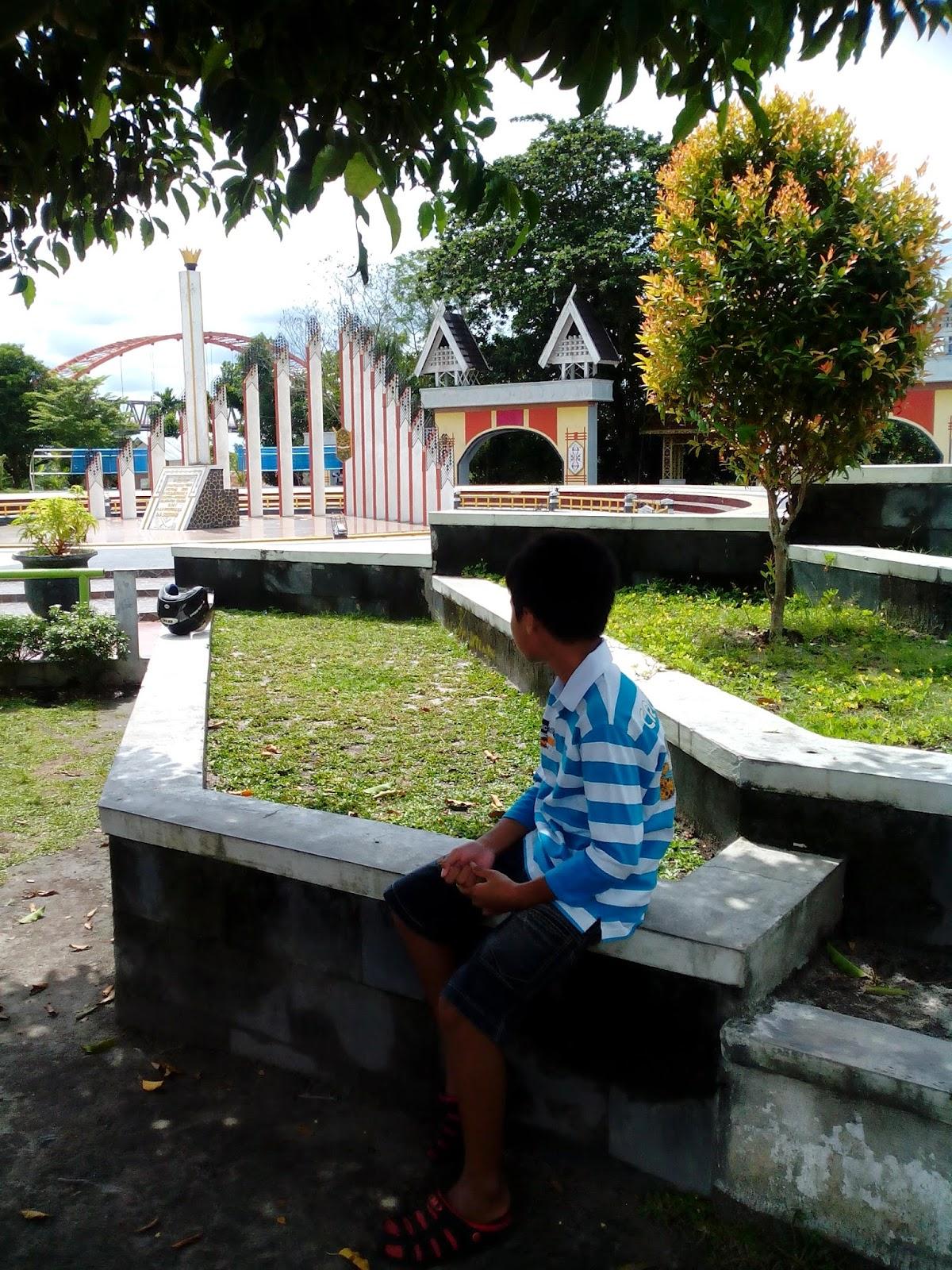 duduk di taman depan tugu