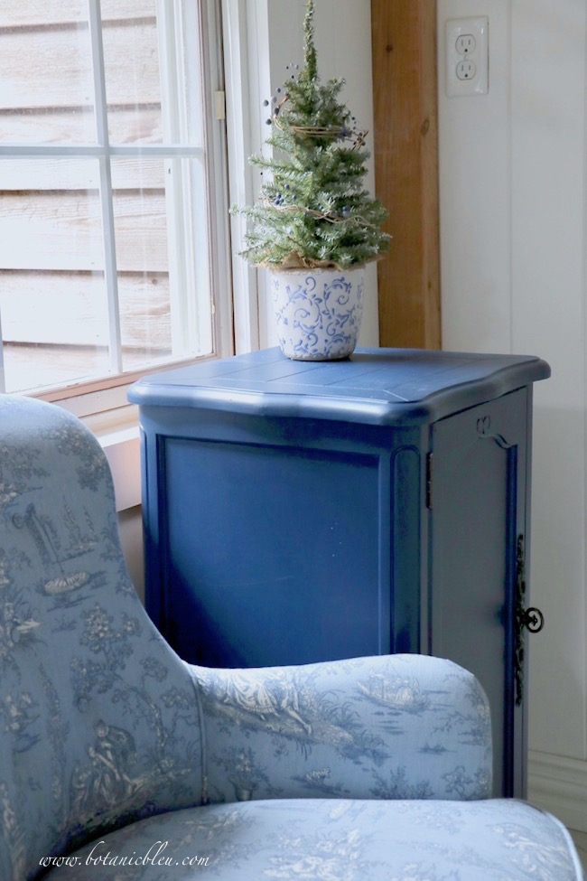 Blue Christmas Laundry Room decorated with artificial small tree in a blue and white scroll flower pot to go with blue toile chair