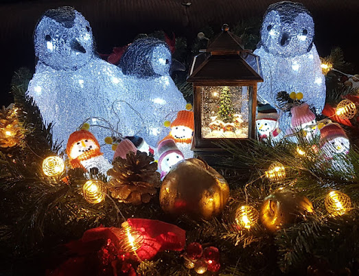 Christmas decorations glowing and lit up. Penguins and lantern etc.