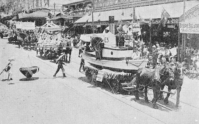 a parade of horses and floats, with a vintage street sweeper assigned to collect the animal droppings