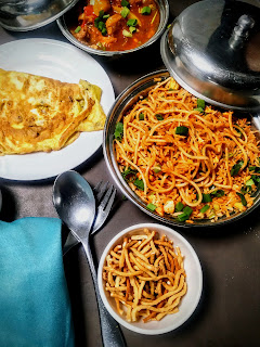 Serving trip rice chicken with fried noodles, schezwan gravy and omlet