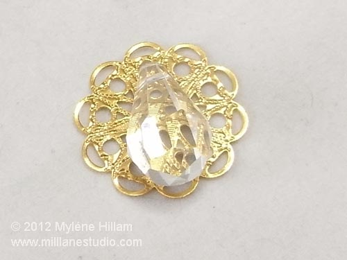 A clear crystal briolette sitting on a round gold filigree