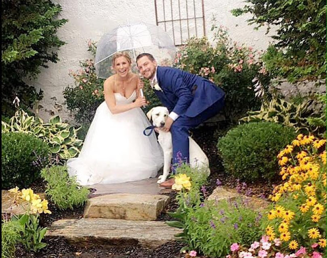 bride, groom and dog in garden