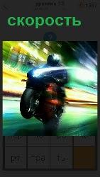 на большой скорости двигается мотоциклист по дороге