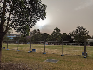 A local park with dried grass and temporary fencing around, the sky is muted and dark despite harsh sun trying to poke through. The park looks dismal and angry.