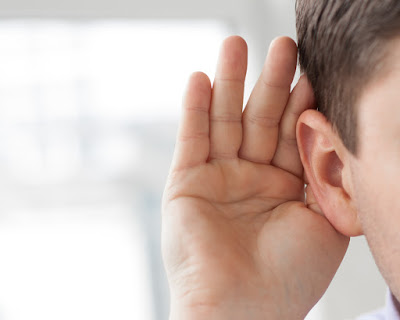 Photo of a person cupping their hand behind their ear to hear better