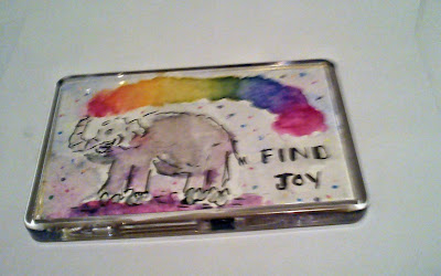 Watercolour fridge magnet in which a happy grey elephant is spouting rainbow dust from its trunk, and the message Find Joy, is hand-lettered i black.
