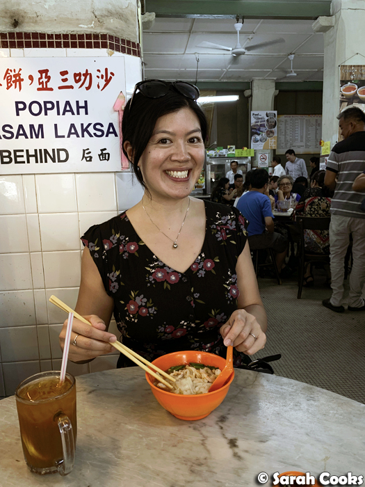 Woman eating noodles and smiling at camera
