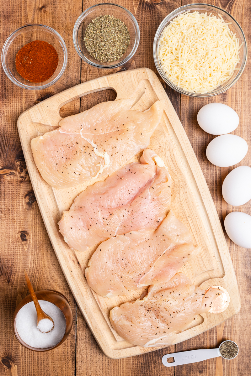 Photo of the ingredients needed to make Keto Parmesan Chicken Cutlets on a wooden table.