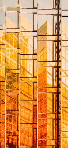 خلفية واجهة مبنى زجاجية ذهبية صفراء وقت الظهيرة