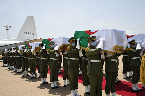 Algerian soldiers carrying the remains of the resistance figures in caskets covered by Algerian flag