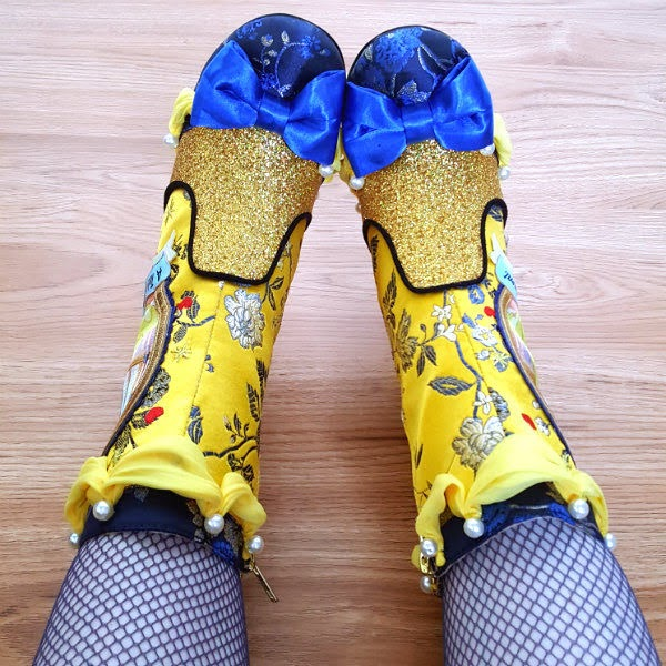 top view of yellow brocade boots with blue bow across toe and rounded toe